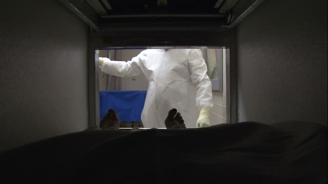 POV push-in - An attendant removes a cadaver from a morgue compartment. / USA