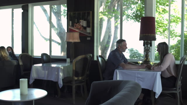 push-in shot of a couple sitting in a restaurant - grandangolo tecnica fotografica video stock e b–roll
