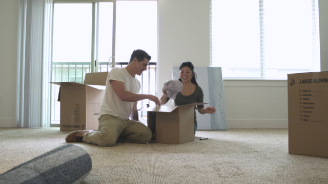 Push-in shot of a couple unpacking a cardboard box