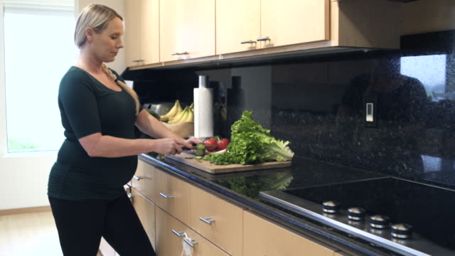 push-in shot of a pregnant woman slicing vegetables - legging stock-videos und b-roll-filmmaterial