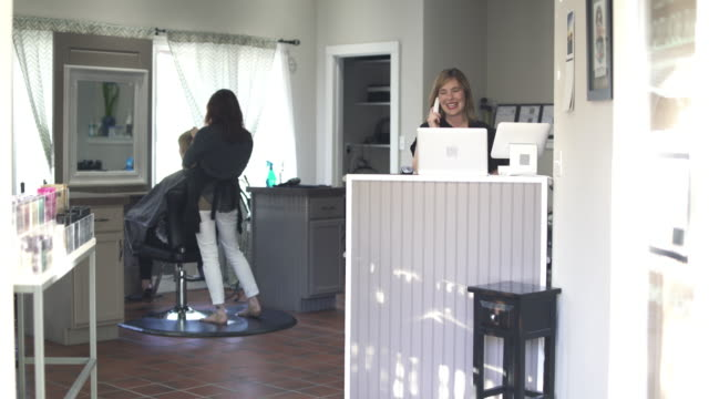 vídeos de stock e filmes b-roll de push-in shot of a receptionist at a hair salon - salão de beleza