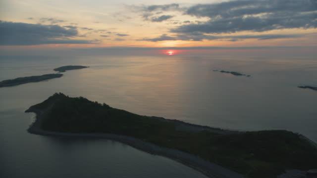 vídeos y material grabado en eventos de stock de push-in shot of the rising sun as seen from above the brewster islands - océano atlántico