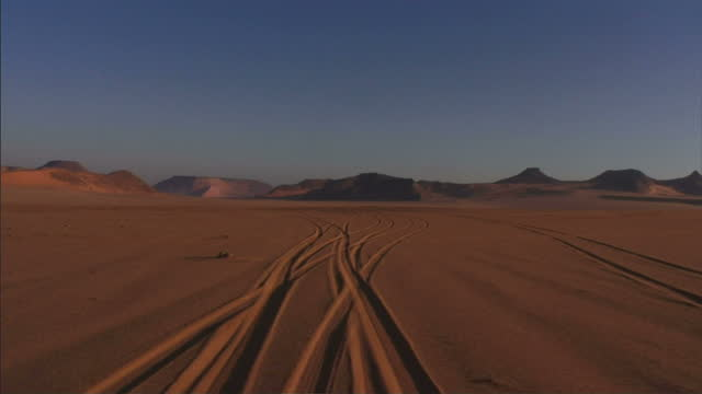 POV push-in - Tire tracks criss-cross through the sand of a vast desert near the mountains / Egypt