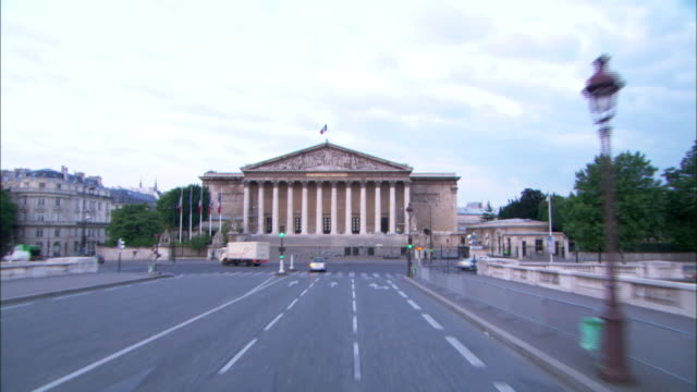 POV push-in - Vehicles turn in front of the French National Assembly building in Paris. / Paris, France
