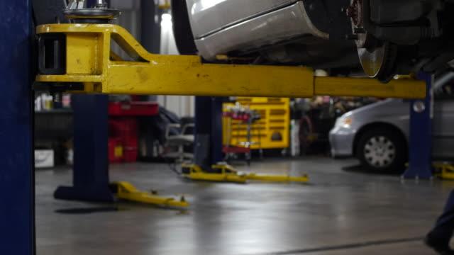 vidéos et rushes de pushing car tire in the auto repair shop - partie de véhicule