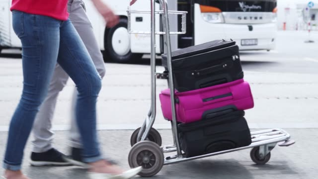 pushing luggage trolley at the airport/ bus station - luggage trolley stock videos & royalty-free footage