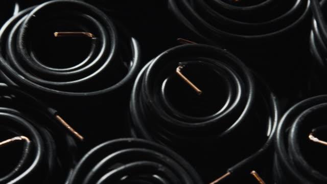 ブラックワイヤー/ホースの大型スプール/コイルのプッシュアウトショット (製造) - 丸くなる点の映像素材/bロール