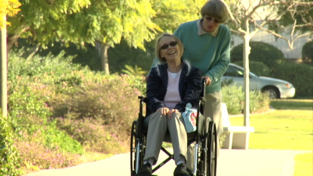 Pushing wheelchair in park HD video