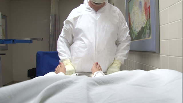 vidéos et rushes de pov push-out - an attendant pushes a cadaver on a tray into a morgue compartment. / usa - autopsie