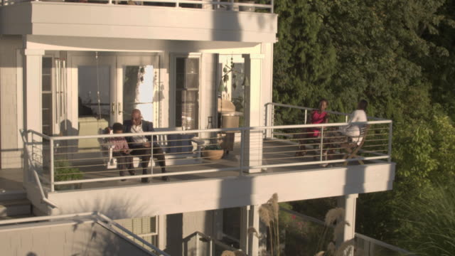 push-out shot of a family resting on a balcony - großfamilie stock-videos und b-roll-filmmaterial