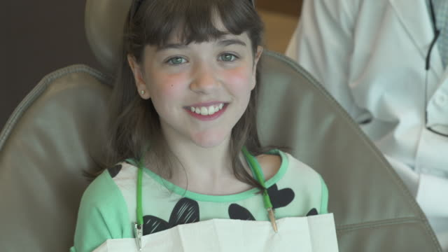 Push-out shot of a girl sitting in a dental chair