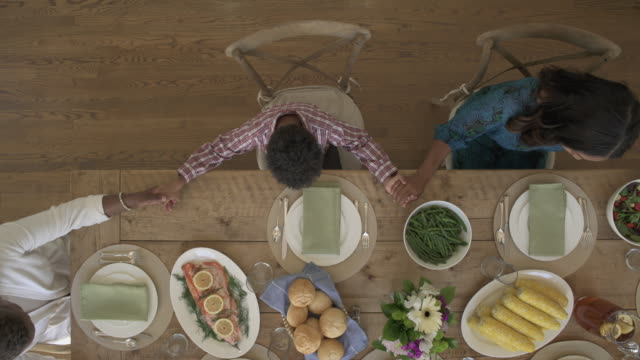 push-out shot of family members praying before meal - frauen über 30 stock-videos und b-roll-filmmaterial