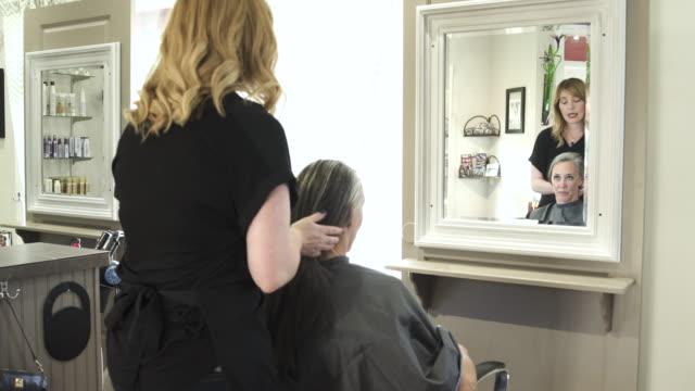 vídeos de stock e filmes b-roll de push-out shot of hairdressers at work - salão de beleza