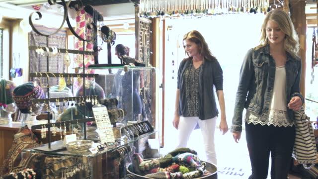 vídeos de stock e filmes b-roll de push-out shot of two women entering a gift shop - entrar