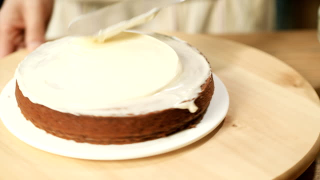 put icing topping on pumpkin cake - pampering stock videos & royalty-free footage