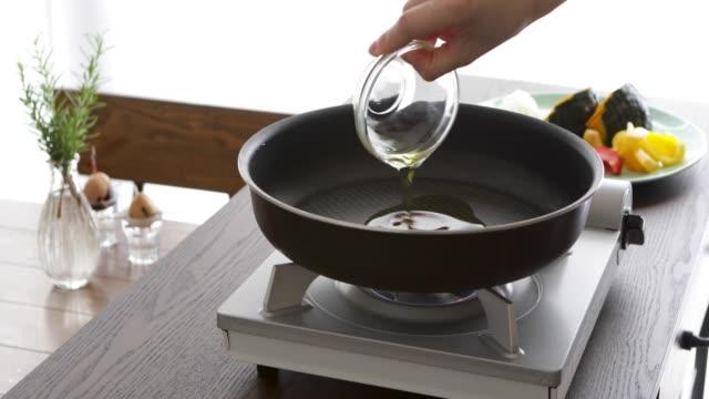 vídeos y material grabado en eventos de stock de poner el aceite, el romero y el ajo en una sartén. - voz