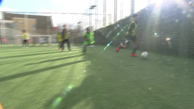 qpr put on free football session for survivors of the grenfell fire england london westway sports centre ext grenfell tower shell seen in distance... - shooting at goal stock videos & royalty-free footage