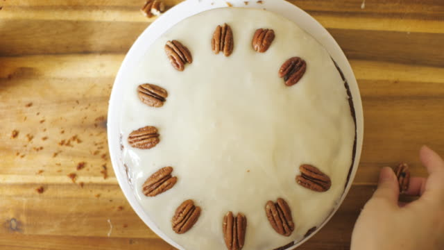 put pecan nut on the carrot cake for decorating - chopping board stock videos & royalty-free footage