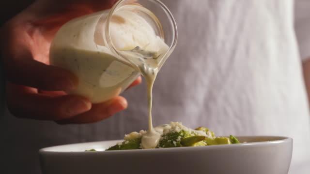 サラダドレッシングをサラダにつけて - サラダドレッシング点の映像素材/bロール