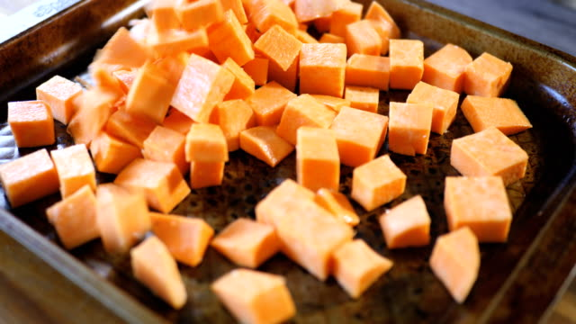 put seasoned sweet potatoes into try for roasting - sweet potato stock videos & royalty-free footage