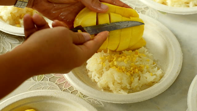 put slice mango into sticky rice on paper plate - paper plate stock videos & royalty-free footage