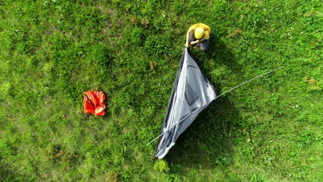 テントを一緒に置いてください。自然の中で若い女性の観光キャンプ。晴れた日の屋外での楽しみ。ドローンからの眺め。 - テント点の映像素材/bロール