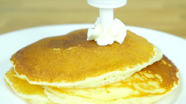 put whipping cream on top of the pancake. Front view. Slow motion.