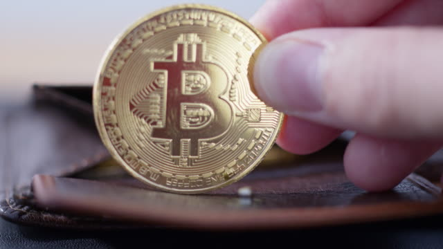 putting a bitcoin coin into a wallet - currency symbol stock videos & royalty-free footage