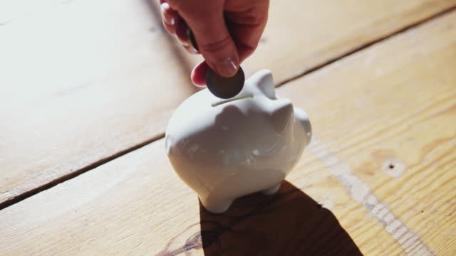 putting a coin in a piggy bank at home. - european union coin stock videos & royalty-free footage