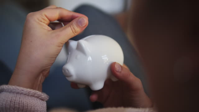 stockvideo's en b-roll-footage met putting a coin in a piggy bank at home. - e commerce