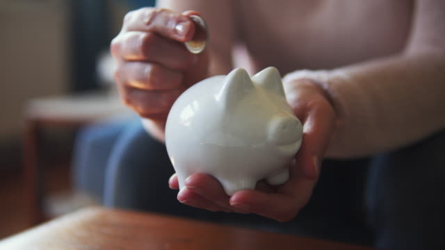 stockvideo's en b-roll-footage met putting a coin in a piggy bank at home. - investering