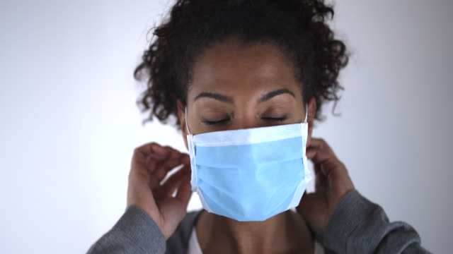 putting a flu mask - protective workwear stock videos & royalty-free footage