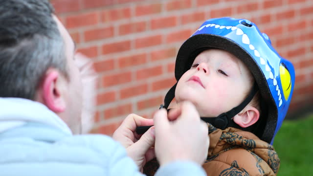putting a helmet on my son - genderblend stock videos & royalty-free footage