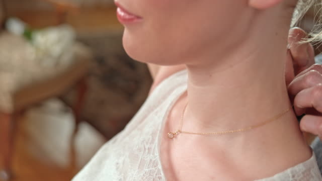 putting a necklace around the bride's neck before the ceremony - necklace stock videos & royalty-free footage
