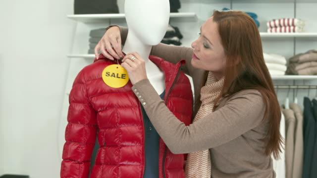 vídeos de stock e filmes b-roll de carrinho de hd: colocar um sinal de venda de roupas - loja de roupa