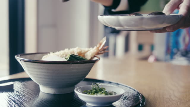 putting a shiitake mushroom topping on the toshikoshi soba (new year's eve noodles) - soba stock videos & royalty-free footage