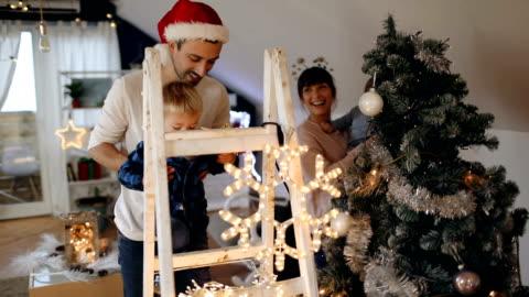setzen einen glänzenden stern auf den christbaum - fairy lights stock-videos und b-roll-filmmaterial