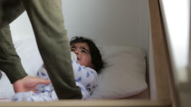 putting baby in the crib - tutina video stock e b–roll