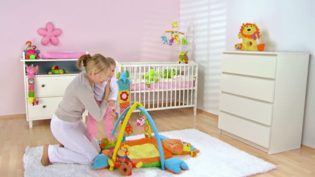 hd crane: putting baby on a playmate - nursery bedroom stock videos & royalty-free footage