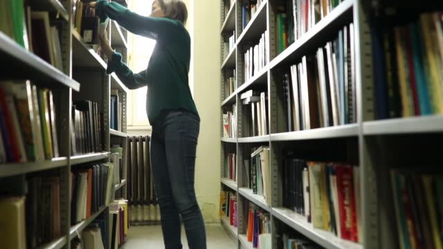 putting back book on bookshelf - librarian stock videos & royalty-free footage