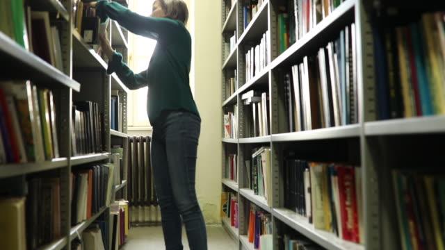er wieder buch im bücherregal - bibliothekar stock-videos und b-roll-filmmaterial