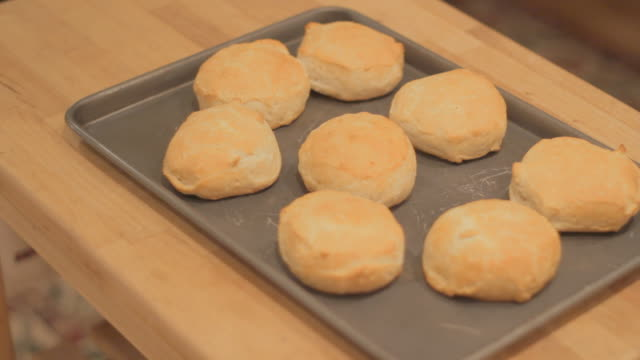 Putting baking plate with fesh baked biscuits on wood table