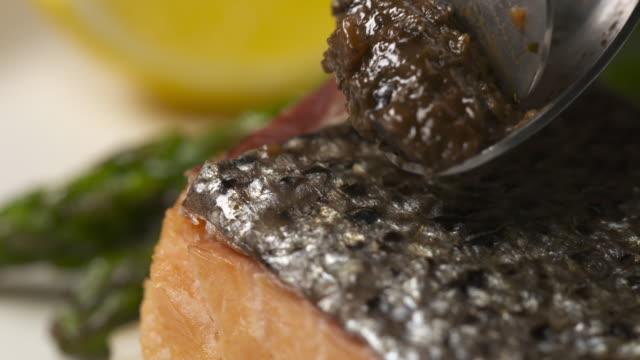 putting black olive sauce onto salmon steak / south korea - black olive stock videos & royalty-free footage