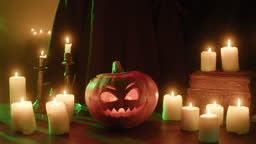 Putting burning candle into carved pumpkin close-up. Jack-o-lantern with fire flame inside standing on wooden table. Halloween symbols, scary face, traditional autumn holiday decorations