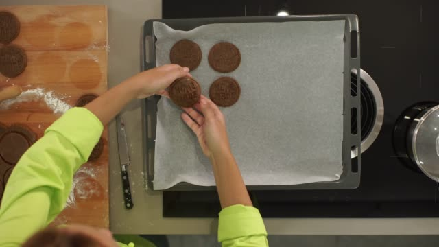 4k putting cookies on baking tray top view - baking tray stock videos & royalty-free footage