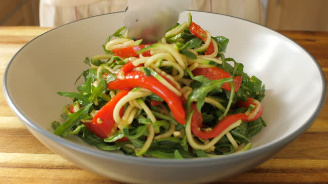 putting courgette noodle and roasted pepper, rocket leaves salad into salad bowl - video stock videos & royalty-free footage