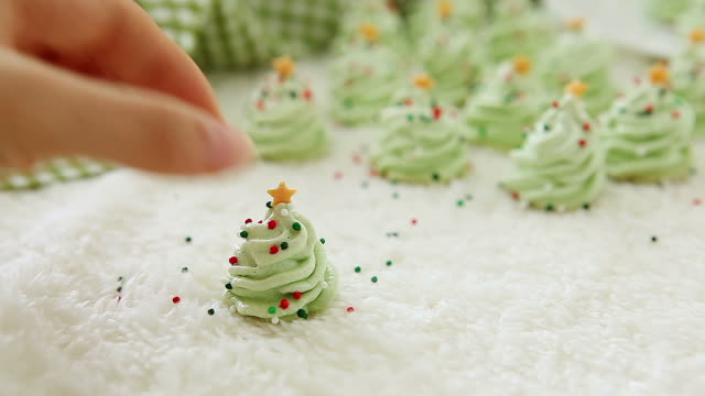 putting down christmas tree shaped meringue cookies - meringue stock videos & royalty-free footage