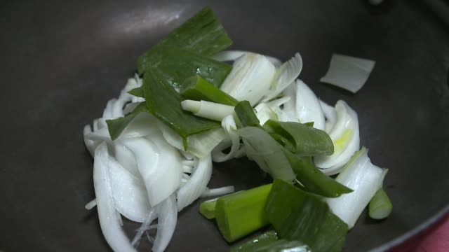putting dried red pepper powder in a frying pan - 赤唐辛子点の映像素材/bロール