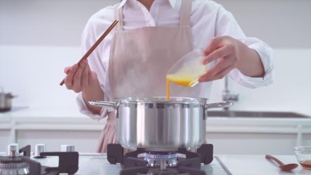 putting egg mixture into tteok mandu guk (korean rice cake soup with dumplings) - korean new year stock videos & royalty-free footage