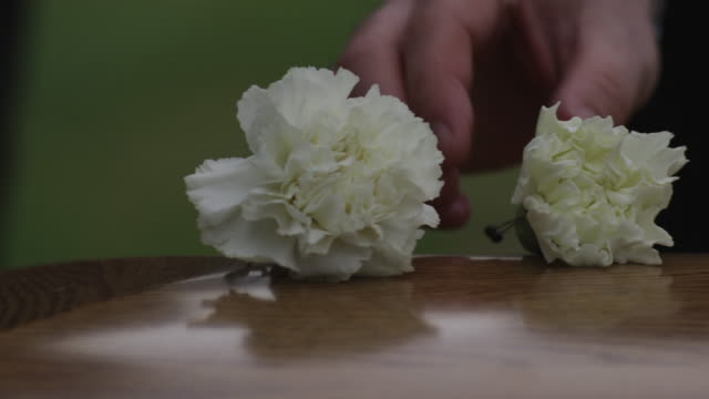 putting flowers on a coffin - begräbnis stock-videos und b-roll-filmmaterial